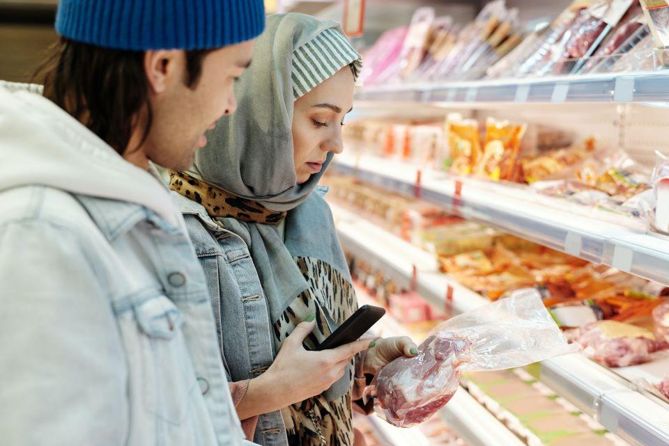 Ein Mann und eine Frau schauen sich Billigfleisch aus einem Supermarktregal an