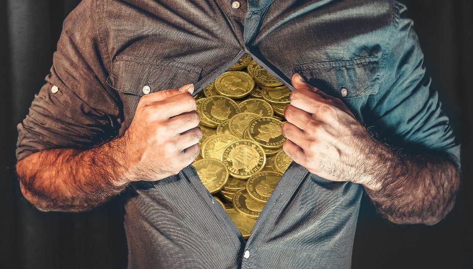 Ein Mann reißt sich das Hemd auf und hat viel Münzgeld in seiner Brust