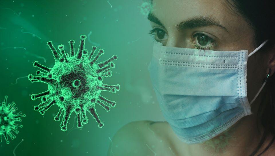Eine Frau mit Maske auf der rechten Seite schaut in Richtung des grünen Corona Virus auf der linken Seite